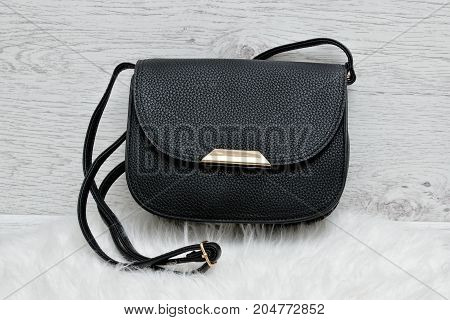 Black Handbag On A White Fur, Light Wooden Background