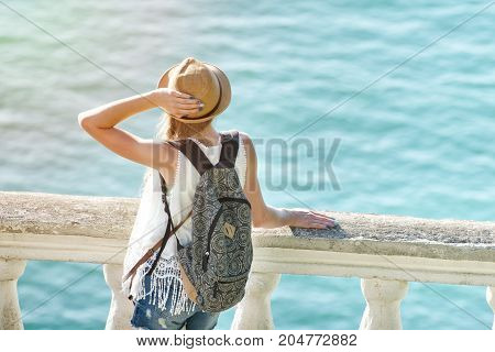 Girl In A Hat And A Backpack Admires Sea. View From The Back