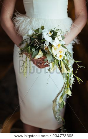 Wedding floral orchids bouquet hanging in bride's hands