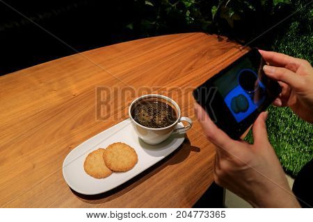 Woman's Hand Taking Picture of Coffee and Cookies with Cell Phone in the Coffee Shop