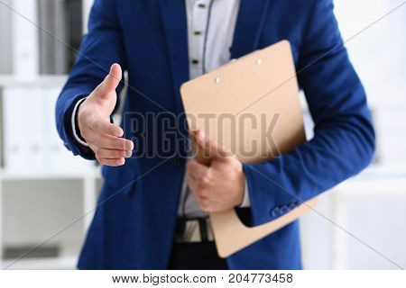 Smiling handsome cheerful man offer hand as hello in office portrait. Serious excellent prospect friendly support service introduction or thanks gesture gratitude invite to participate concept