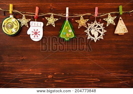 Wooden And Felt Christmas Decorations And Christmas Lights On A Rope On The Brown Wooden Background,