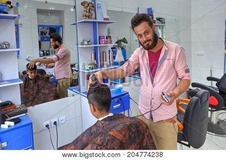 Fars Province Shiraz Iran - 18 april 2017: Iranian hairdresser makes hairstyle for teenage boy.