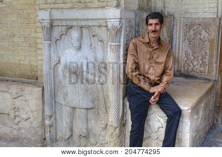 Fars Province Shiraz Iran - 18 april 2017: One mature man is sitting near the facade bas-relief.