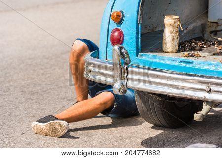 The Legs Of A Man Under The Car, Vinales, Pinar Del Rio, Cuba. Car Repairs. Close-up.