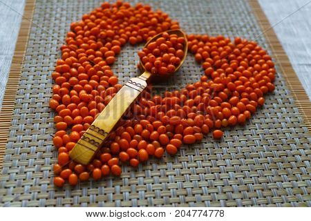 Brightly orange sea-buckthorn berries are scattered on the table.