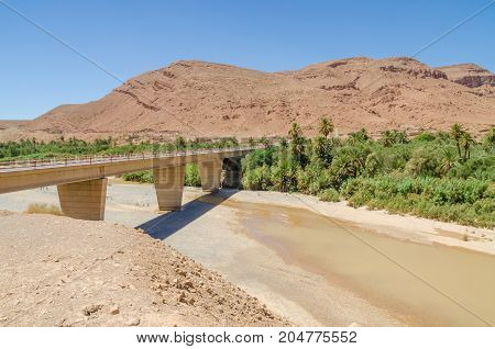 Bridge spanning over dry river bed with some water, mountains and palms in Morocco, North Africa.