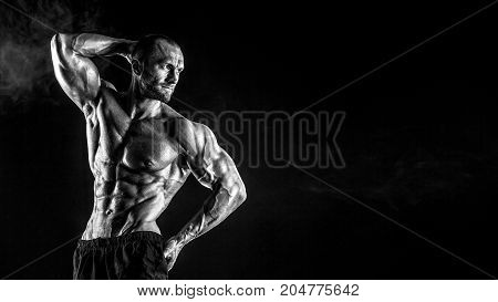 Strong bald bodybuilder with six pack. Strong bodybuilder man with perfect abs, shoulders, biceps, triceps and chest flexing his muscles on black studio background. Copy space