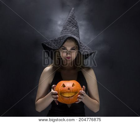 Cheeful witch with smoky pumpkin in her hands on black background