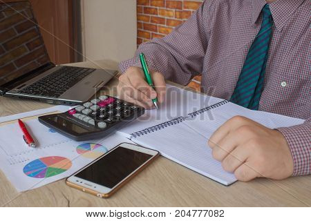 Pen on paperwork accounts with man use computer to save data in background. accounting concept. Man hand with pen calculator and computer on wooden table. saving money or insurance concept