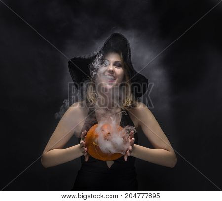 Laughing witch with smoky pumpkin in her hands on black background