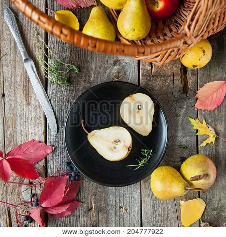 Autumn Harvest Concept - Cut Fresh Ripe Pear On The Black Plate And Group Of Yellow Pears In The Bas