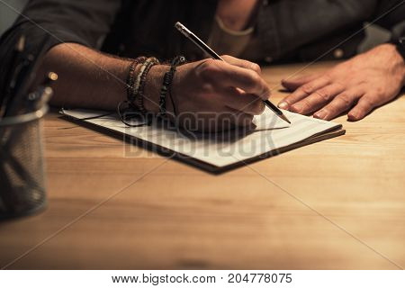 Musician Writing In Music Notebook