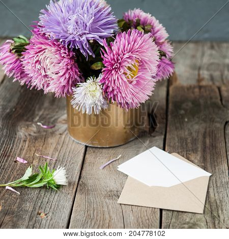 Multicolor Aster Flowers Bouquet, Blank White Greeting Card And Craft Paper Envelope On Rustic Woode