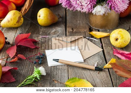 Thanksgiving Background With Seasonal Fruits, Flowers, Greeting Card And Few Craft Envelopes On A Ru
