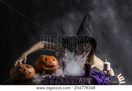 Attractive witch in the wizarding lair with smoke going from her mouth.Halloween