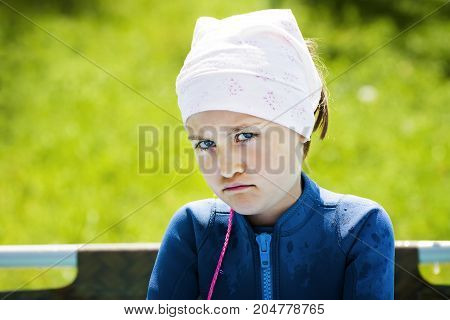 Portrait of girl with angry upset face expression outdoor.