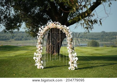 Beautiful wedding arch of flowers and hanging beads on a background green field with trees