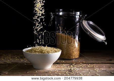 rice grains falling into a white bowl beside a glass jar with rice on a rustic wooden table against a dark background food concept against hunger and for world nutrition selected focus