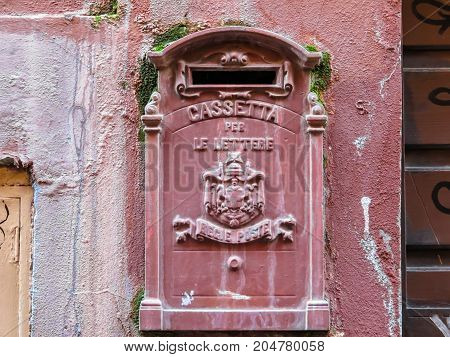 Old red mailbox on the street of Rome, Italy