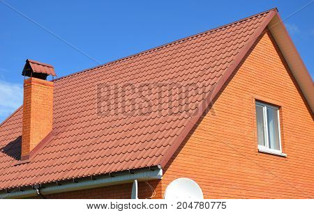 Roof repair. Roofing construction. Brick House with red metal roof tile and chimney outdoor