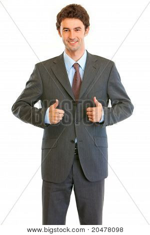 Smiling young businessman showing thumbs up gesture isolated on white