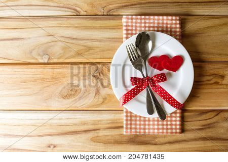 red heart shape with White empty plate with fork and spoon on wooden table for love dinner concept