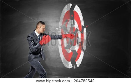 A businessman wears boxing gloves and breaks a chalk drawing of a round archery target. Success and failure. Reaching your goal. Break your record.