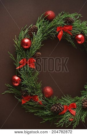 Christmas vitage fir branches decorated with red globes, and red bows. Copy space.Brown background.