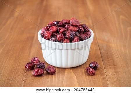 Dried cranberries in bowl on wooden background