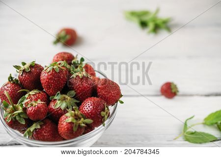 Glass plate with ripe red strawberries and green mint leaves on a white wooden table. Macro photo of ripe strawberries.