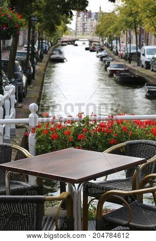 alfresco table of a bar near a wagterway canal with boats