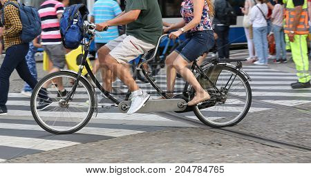 Man And Woman Pedal With Tandem In Urban Road
