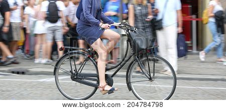 Long Legs Of Woman While Fast Pedal On Bicycle And The Backgroun