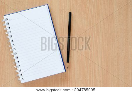 White note book and black pencil on beech color background with copy space.