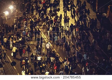 Crowd of anonymous people walking on night Voronezh street, view from above or top view