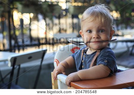 Little boy is sitting in a cafe with a spoon