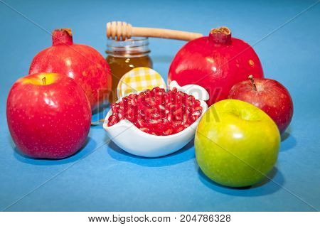 Jewish symbols, the Jewish New Year Rosh Hashanah concept - apple shaped plate with red pomegranate seeds on a blue background with honey. Rosh Hashanah greeting.