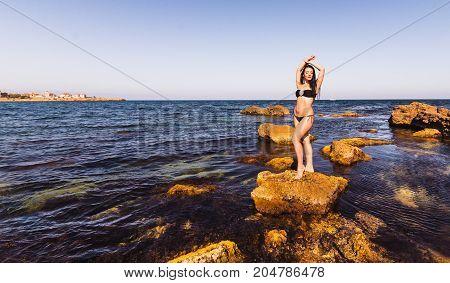 Sexy curvy brunette woman on a beach