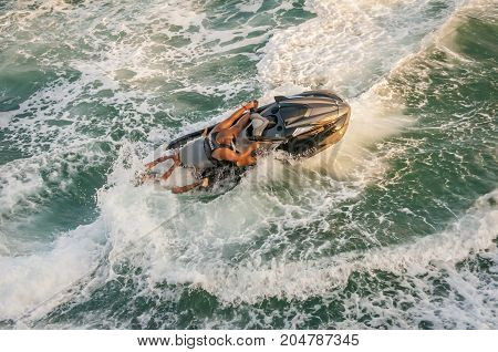 ACCO (ACRE), ISRAEL. September 16, 2017. Young Arab Muslim men driving a boat, showing the crazy ride to public at the ancient Acco fortress. Men in the boat in the raging sea.