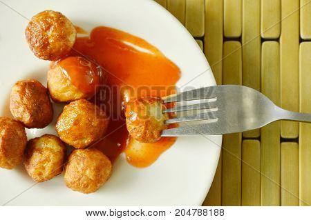 crispy fried pork ball dressing chili sauce stabbing in fork