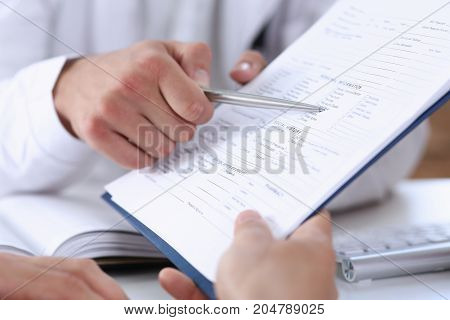 Male Doctor Hand Hold Silver Pen And Showing Pad