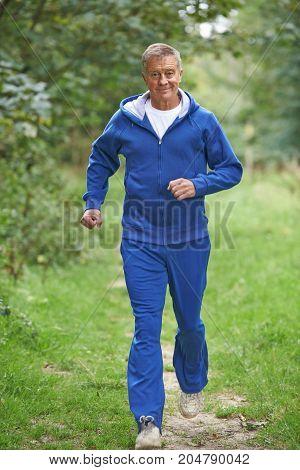 Senior Man In Tracksuit Running Through Countryside