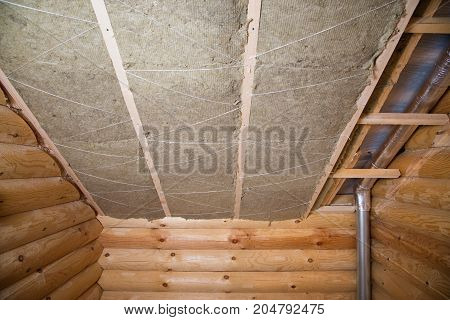 wall heat isolation with mineral wool in wooden house, building under construction.
