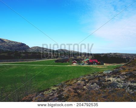 A Traditional Wooden Red House Cabin Bellow Rocky Hill. House In Classic Norway Design