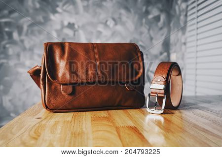 Vintage travelling for men's accessories a brown bag and belt put on modern wooden desk table in the office with loft concrete wall style.