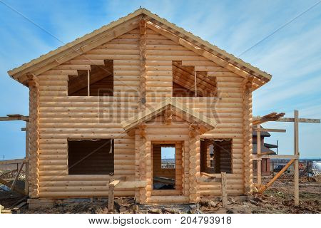 Unfinished, ecological wooden house from beams in countryside.
