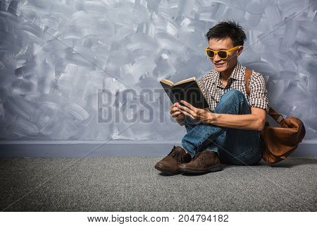 Hipster asian man reading a bible book believe in God and faith vintage hipster fashion style.