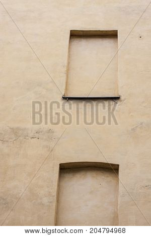 Empty windows on yellow wall. Window hole on solid wall. Cheap appartments without view
