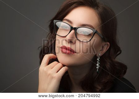 Gorgeous young brunette woman wearing glasses with black frames earrings touching chin looking away.